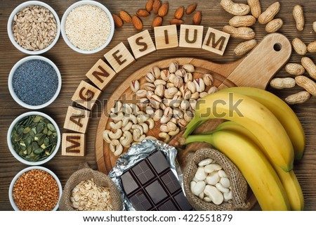 Products containing magnesium: bananas, pumpkin seeds, blue poppy seed, cashew nuts, beans, almonds, sunflower seeds, oatmeal, buckwheat, peanuts, pistachios, dark chocolate and sesame seeds - stock photo