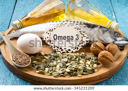 Products - source fatty acids Omega 3 (mackerel, camelina oil, rapeseed oil, organic egg, pumpkin and flax seeds, walnuts) on a round wooden board - stock photo