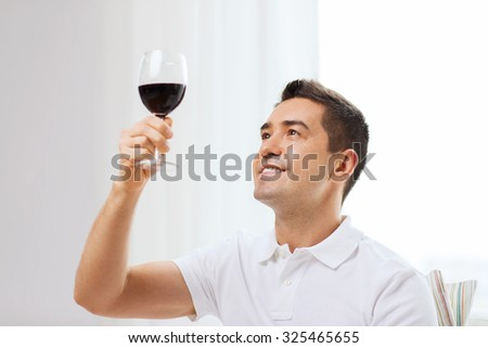 profession, drinks, leisure and people concept - happy man drinking red wine from glass at home - stock photo