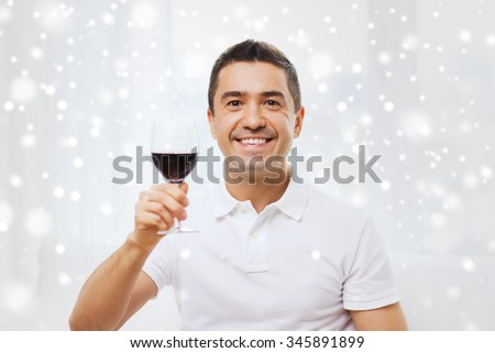profession, drinks, leisure, holidays and people concept - happy man drinking red wine from glass at home over snow effect - stock photo