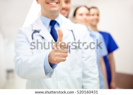 profession, people, healthcare, gesture and medicine concept - close up of happy medics or doctors at hospital corridor showing thumbs up