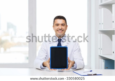 profession, people, technology, advertisement and medicine concept - smiling male doctor in white coat showing tablet pc computer blank screen in medical office