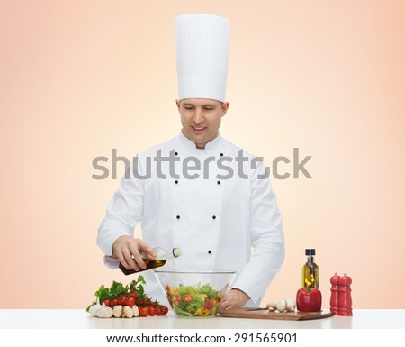 profession, vegetarian, food and people concept - happy male chef cooking salad over beige background - stock photo