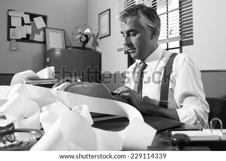 Professional accountant working with adding machine tape in vintage office. - stock photo