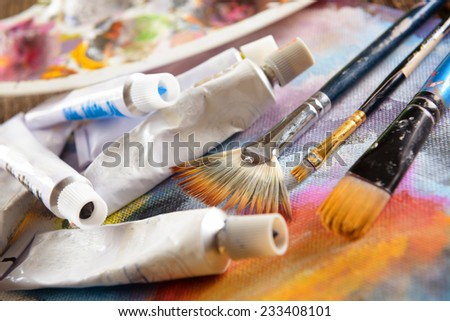 Professional acrylics paints with artistic brushes on canvas - stock photo
