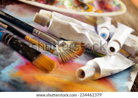 Professional acrylics paints with artistic brushes on canvas with palette in background - stock photo
