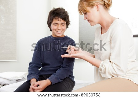 Professional acupuncturist showing needles to young patient