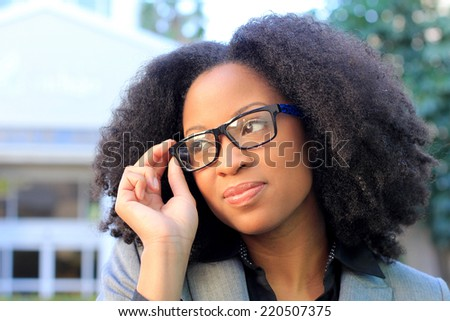 Professional African American Business Woman With Black Hair Outside Natural Pose Holding Glasses Smiling  - stock photo