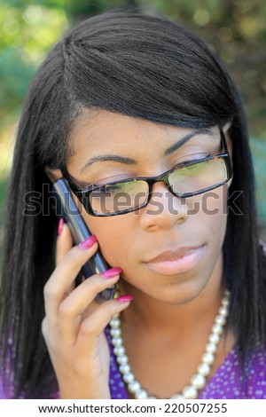 Professional African American Business Woman With Black Hair Outside Natural Pose Wearing Glasses and Pearls Talking On The Phone  - stock photo