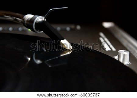 Professional analog DJ sound equipment playing music. Vinyl record on turntable player. Dj audio equipment. Focus on turntable needle. Disc jockey with turntables for party