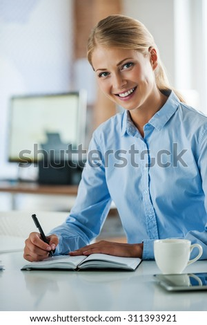 Professional and ambitious.Smiling young businesswoman in formalwear writing in note pad and looking at camera while sitting at her working place - stock photo