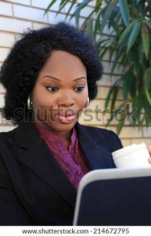 Professional and Attractive African American Business Woman Holding Coffee Working on Laptop Wearing Black Suit - stock photo