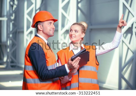 Professional architects are standing and holding a tablet. The woman is explaining to the man in helmet her ideas about building. She is pointing her finger up. They are smiling - stock photo