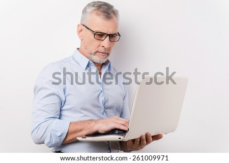 Professional at work. Confident senior man in shirt and eyeglasses working on laptop while standing against grey background - stock photo