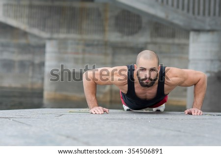 Professional athlete fitness trainer. Muscular male sportsman is training himself and doing pushups. Outdoors workout fitness healthy concept.