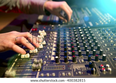 Professional audio mixing console with faders and adjusting knobs - stock photo