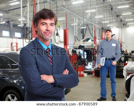 Professional auto mechanic  and manager in auto repair shop. Garage. - stock photo