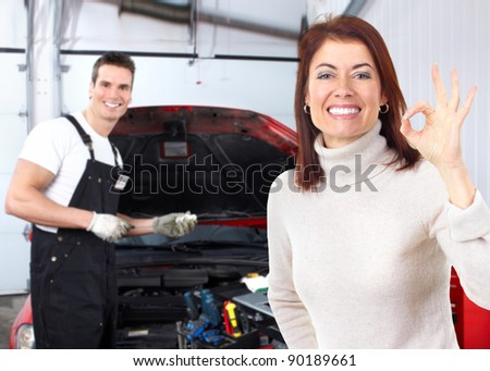 Professional auto mechanic and woman in auto repair shop. Garage. - stock photo
