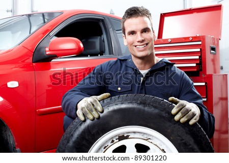 Professional auto mechanic changing a tire in auto repair shop. Garage. - stock photo