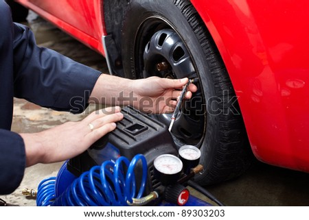 Professional auto mechanic changing a tire. in auto repair shop. Garage. - stock photo