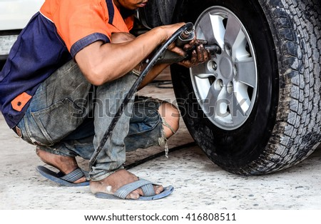 Professional auto mechanic changing a tire in auto repair shop.Mechanic changing a wheel of a modern car in a workshop.Inside a garage