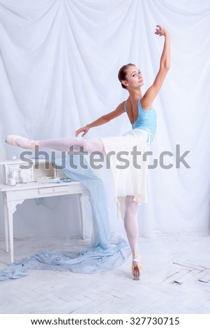 Professional ballerina dancer posing against the white dressing room - stock photo