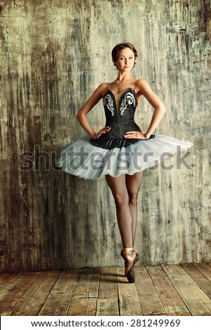 Professional ballet dancer posing at studio over grunge background. Art concept. - stock photo