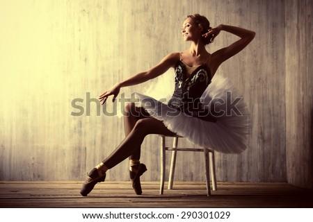 Professional ballet dancer posing at studio over grunge background. Art concept. - stock photo
