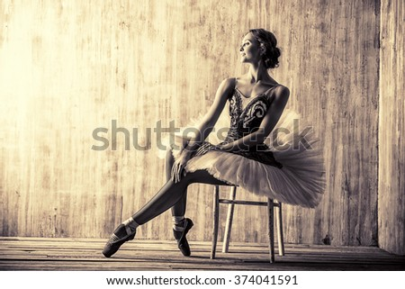 Professional ballet dancer posing at studio over grunge background. Art concept. Toned photo, vintage style. - stock photo