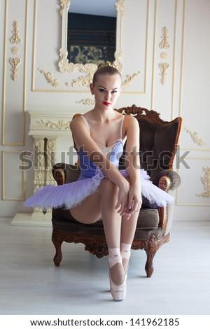 Professional ballet dancer posing in classic interior, studio shot - stock photo