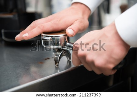 Professional barista pressing coffee with his hand