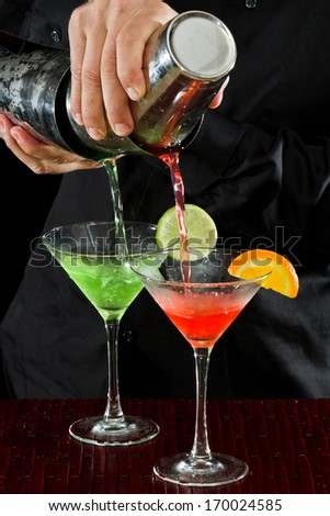 professional bartender pouring two martinis at the same time in  a fluid motion - stock photo