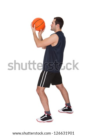 Professional basketball player throwing the ball. Isolated on white