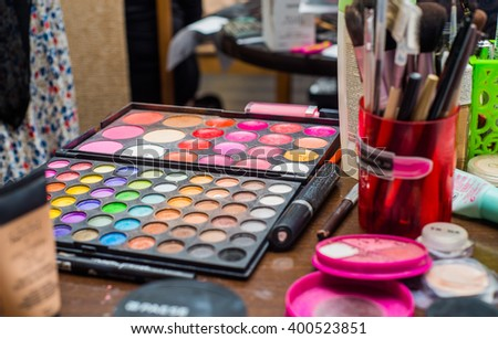 professional beautician with brushes and a variety of shadows and blush of makeup artist - stock photo