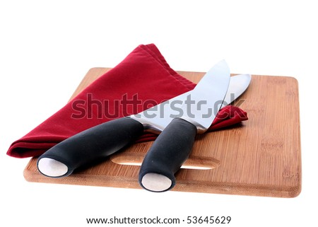 Professional big cook knifes on darkly red napkin and a kitchen board.