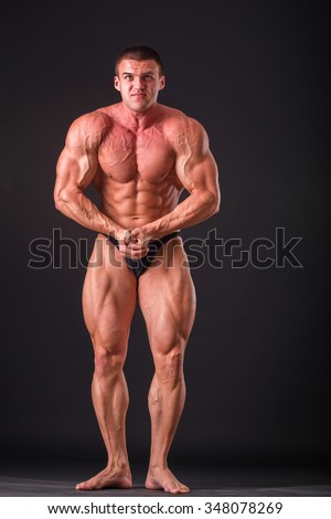 Professional bodybuilder shows his body on a dark background. Muscular body athlete. The result achieved by training and hard work on themselves. Photos for sporting magazines, posters and websites.