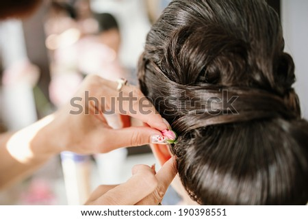 Professional bridal stylist busy with a happy bride and attaching a tender rose flower in her coiffure