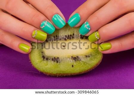 Professional bright manicure. Beautiful color manicure. The combination of the photo manicure and fresh fruit. Women's hands. - stock photo