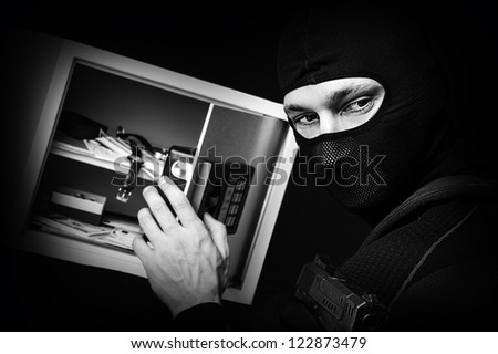 Professional burglar in black ski mask opened a small safe, holding hand gun and aiming - stock photo