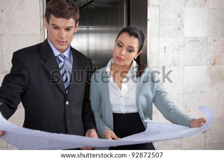 Professional business people reviewing business plan in office - stock photo
