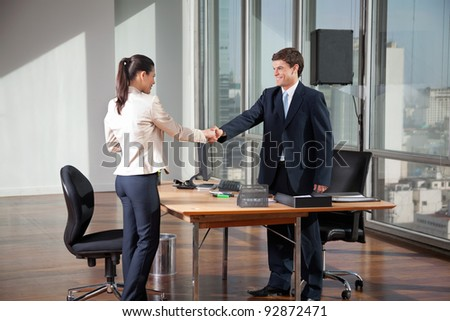 Professional business people shaking hands over a deal in office - stock photo
