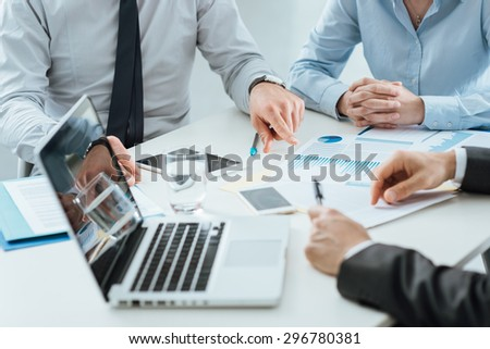 Professional business team working together at office desk discussing during a meeting, efficiency and teamwork concept - stock photo