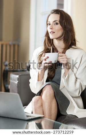 Professional business woman enjoying a fresh coffee while using her laptop computer