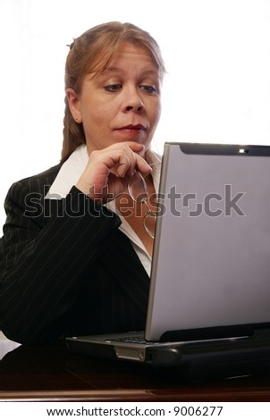 Professional business woman raising her eyebrows at something on the computer.