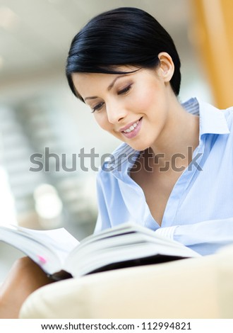 Professional business woman rests at the sofa reading book at the hall - stock photo