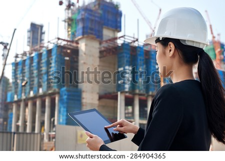 professional business woman supervising construction site with hard hat protection at work - stock photo