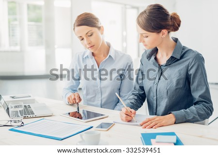 Professional business women working together at office desk and using a touch screen tablet - stock photo