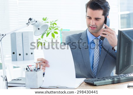 Professional businessman checking at his notebook while on the phone - stock photo