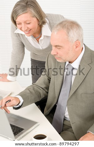 Professional businesspeople behind office table with laptop