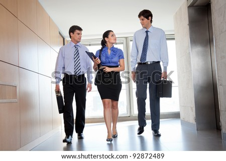 Professional businesspeople walking in office corridor - stock photo